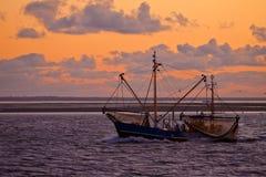 Sonnenuntergang in Meer mit einem Fischerboot in der Frontseite stockbilder