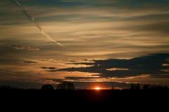 Sonnenuntergang mit Baumschattenbild, roter Sonne und nettem Himmel Stockfoto