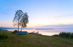 Sonnenuntergang mit Booten nahe dem Sommerseeufer Stockbilder