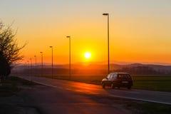 Sonnenuntergang mit einem Auto, das vorbei überschreitet Lizenzfreie Stockfotografie