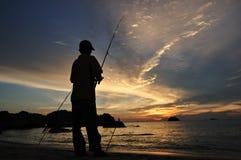 Sonnenuntergang mit einem Fischenmann. lizenzfreie stockbilder