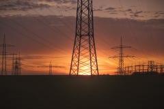 Sonnenuntergang mit Freileitungsmasten Stockbilder