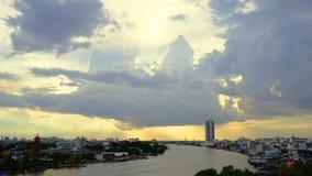 Sonnenuntergang mit großen dunklen Wolken auf dem Fluss in Bangkok Stockfoto