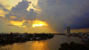 Sonnenuntergang mit großen dunklen Wolken auf dem Fluss in Bangkok Stockbild