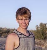 Sonnenuntergang mit lächelndem attraktivem Jungen in der Joshua-Baumlandschaft Lizenzfreie Stockbilder