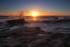 Sonnenuntergang mit orange Wolken und Spray von den Wellen, die auf Felsen an Dunraven-Bucht, Tal von Glamorgan, Südwales zusamme lizenzfreies stockfoto