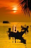 Sonnenuntergang mit Palme und Booten auf tropischem Strand Lizenzfreies Stockfoto