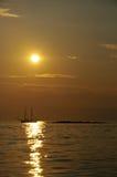 Sonnenuntergang mit Schattenbild eines Bootes Stockbild