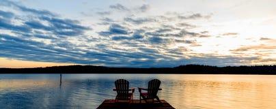 Sonnenuntergang mit St?hlen auf einem See stockfotos