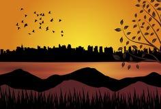 Sonnenuntergang mit Stadt und See lizenzfreie stockbilder