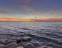 Sonnenuntergang mit Steinen auf dem See Lizenzfreies Stockfoto