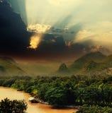 Sonnenuntergang mit Strahlen über Fluss Lizenzfreies Stockfoto