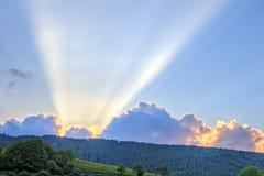 Sonnenuntergang mit Strahlen des Lichtes über Gebirgsrücken Stockfotografie