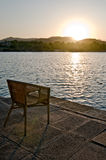 Sonnenuntergang mit Stuhl nahe See Lizenzfreie Stockbilder