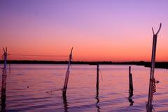 Sonnenuntergang mit violetten Farben auf dem Wasser stockfotos