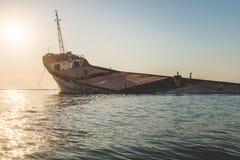 Sonnenuntergang mit Wrackschiff in Schwarzem Meer Stockbild