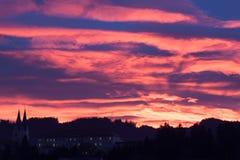 Sonnenuntergang-Mystiker - mit Kirche und Dorf Stockbilder