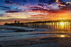 Sonnenuntergang am Ozeanufer-Pier Stockbilder