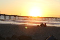Sonnenuntergang am Pier im Ozean-Strand Lizenzfreies Stockfoto