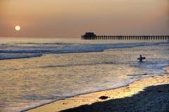 Sonnenuntergang am Pier im Ozeanuferstrand, Kalifornien. Stockfotos