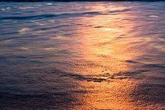 Sonnenuntergang reflektierte sich im Schaumgummi auf Strand Stockbild