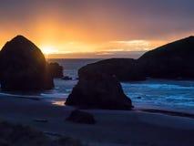Sonnenuntergang am sandigen Strand mit Seestapeln Stockfotos