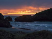 Sonnenuntergang am sandigen Strand mit Seestapeln Lizenzfreie Stockfotos