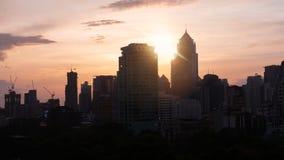 Sonnenuntergang am Schattenbildstadtbild und am orange Himmel lizenzfreie stockfotografie