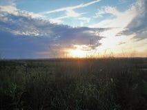 Sonnenuntergang skys über der Wiese Lizenzfreie Stockfotografie