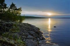 Sonnenuntergang am steinigen Ufer von Ladoga See lizenzfreies stockfoto