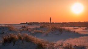 Sonnenuntergang am Strand als Cape May Leuchtturm steht im Hintergrund am südlichsten Tipp von NJ lizenzfreie stockbilder