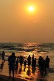 Sonnenuntergang am Strand- und Leuteschattenbild stockfotografie