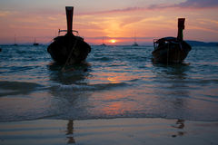 Sonnenuntergang am tropischen Strand mit traditionellen thailändischen Booten stockfotos