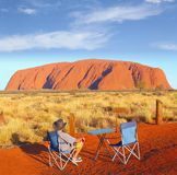 Sonnenuntergang Uluru, Australien des kampierenden Stuhls des Mannes stockbild