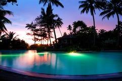 Sonnenuntergang und belichteter Swimmingpool Stockfotos