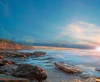 Sonnenuntergang und Blendenfleck durch das Ufer Stockfotografie