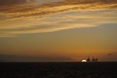 Sonnenuntergang und Bohrinsel Lizenzfreies Stockfoto