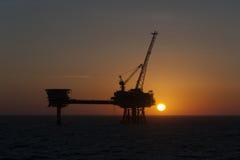 Sonnenuntergang und Bohrinsel Stockfotos