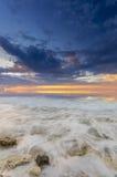 Sonnenuntergang und die Wellen, die auf dem felsigen Ufer einhüllen Lizenzfreie Stockfotografie