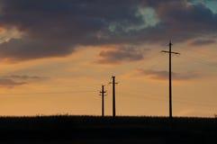 Sonnenuntergang und drei elektrische Masten Stockbilder