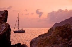 Sonnenuntergang und ein Segelboot Stockfotografie