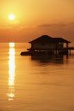 Sonnenuntergang und ein Wasserbungalow im Indischen Ozean Stockbilder