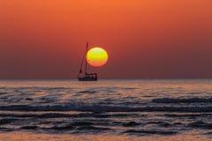 Sonnenuntergang und eine Yacht, welche die Sonne berührt Stockfotos