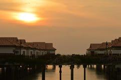 Sonnenuntergang und Häuser Überwasser Stockfotografie
