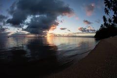 Sonnenuntergang und Kokosnuss-Palmen auf Tropeninsel lizenzfreie stockfotos