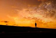 Sonnenuntergang und laufender Mann. Stockbild