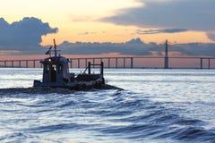Sonnenuntergang und Schattenbild des Bootes kreuzend der Amazonas, Brasilien Lizenzfreie Stockfotografie