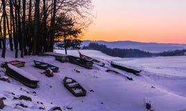 Sonnenuntergang und schneebedecktes Ufer mit Booten Lizenzfreies Stockbild
