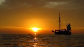 Sonnenuntergang und Segelnlieferung auf dem Meer lizenzfreies stockfoto