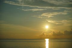 Sonnenuntergang und Sonnenaufgang mit drastischem Himmel über Ozean lizenzfreies stockfoto